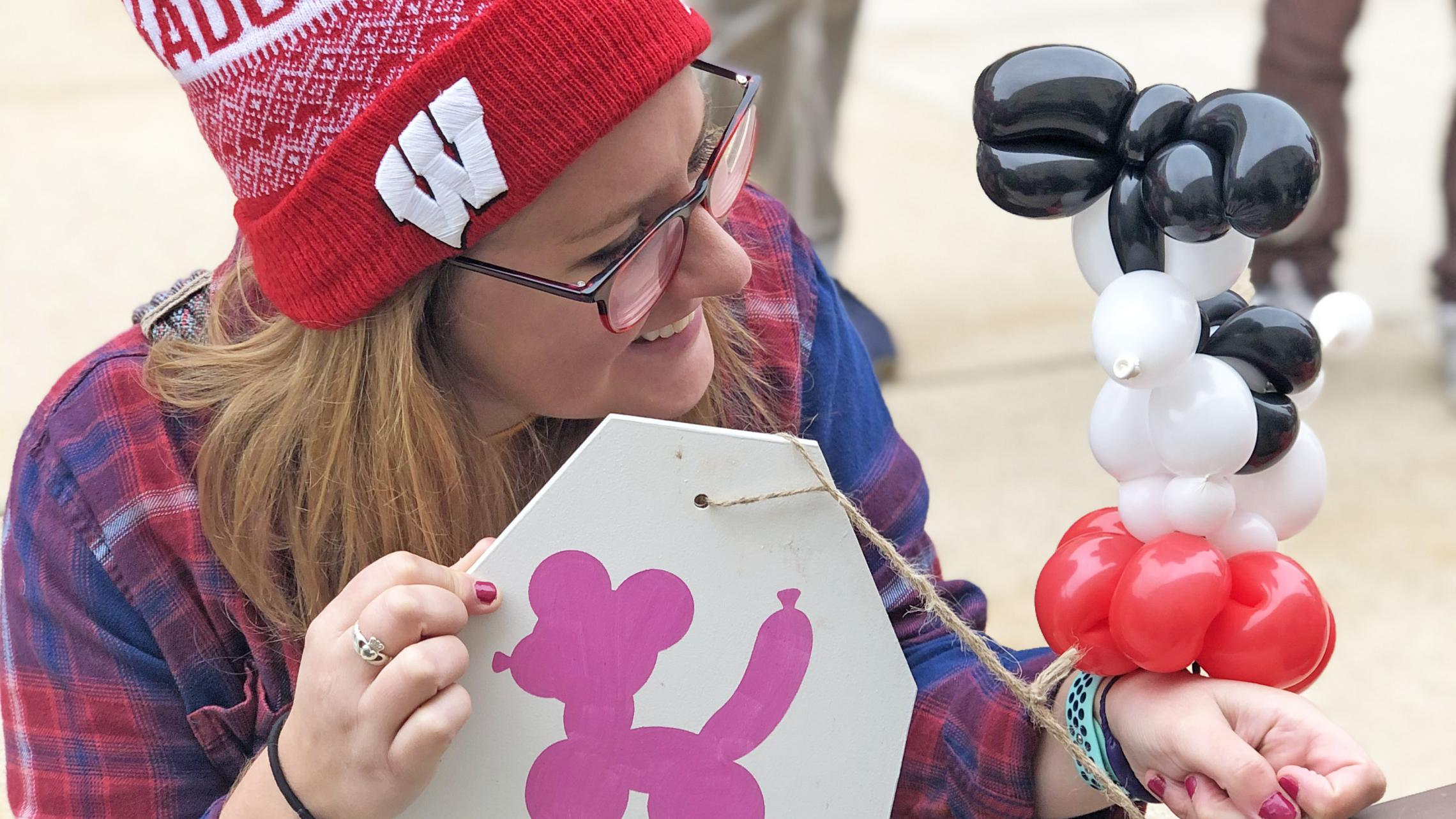 Residents enjoying ULI's second annual tailgate during the Wisconsin Badgers Football Game with balloon figures from Funny Faces