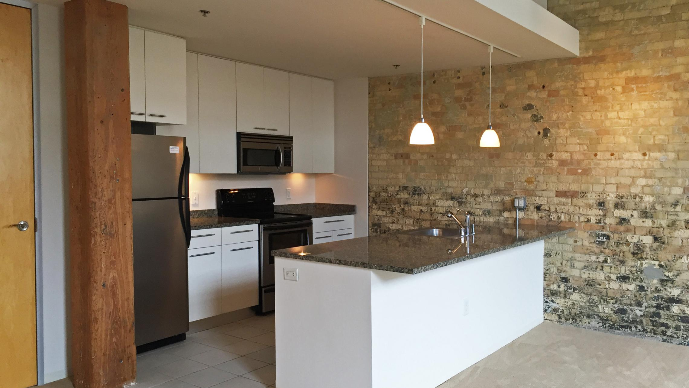 ULI Tobacco Lofts - E208 - Exposed Brick and Beams in Kitchen